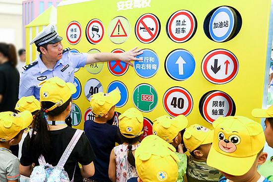 """02.交警在""""安安驾校""""为小朋友讲解交通安全标识"""